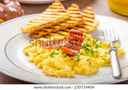 Scrembled eggs with panini toast and donut, fresh orange juice for sure and healthy - stock photo
