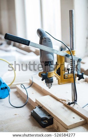 Screw and electric drill on wood at workshop