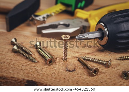 Screw being screwed into a piece of wood - stock photo