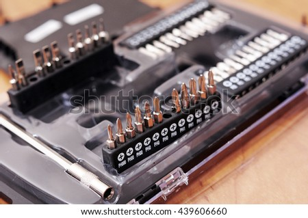 Screw being screwed into a piece of wood, Tool box with tools close-up - stock photo