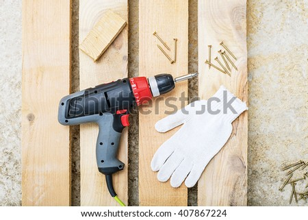 screw gun or electric screwdriver on wooden background with workers building white gloves, Cordless drilling screwdriver machine  - stock photo