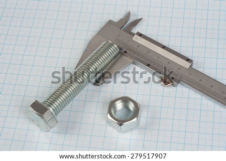 Screw, Nuts and caliper on  graph paper background