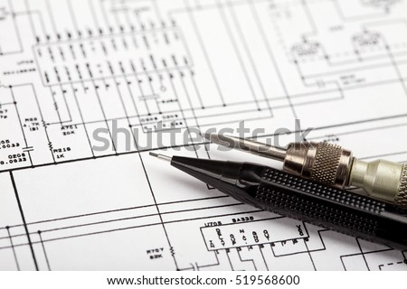 Screwdriver and pencil on a schematic diagram background