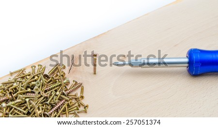Screwdriver with screws on a wood plank suggesting craftsman and carpentry work with manual tools - stock photo