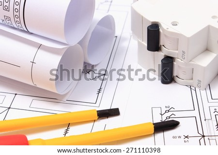 Screwdriver, work tools, rolls of electrical diagrams and electric fuse lying on construction drawing of house, accessories for engineering work - stock photo