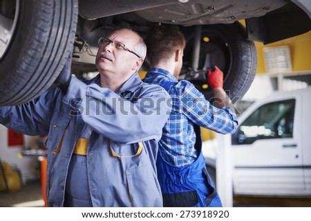 Screwing tires by two mechanics