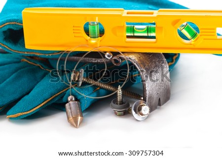 Screws for fixing the roof, plumb, level and gloves - stock photo