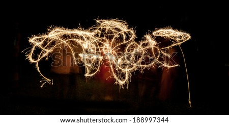 Scribble written with sparklers against a black background - stock photo