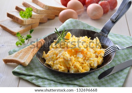 Scrmbled eggs with toast, served in a pan - stock photo