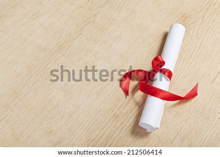 Scroll of paper with a red ribbon on a wooden surface. - stock photo