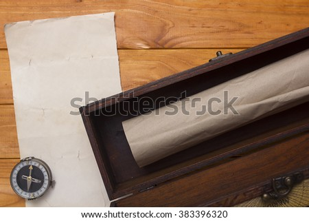 Scroll to a box and compass on a wooden background