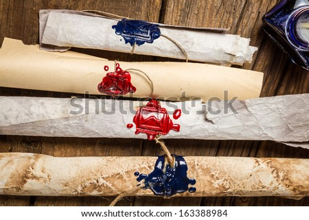 Scroll with the envelope symbol imprinted in sealing wax - stock photo