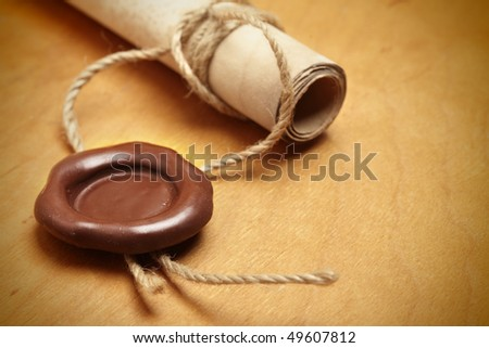 Scroll with wax seal on a wooden table - stock photo