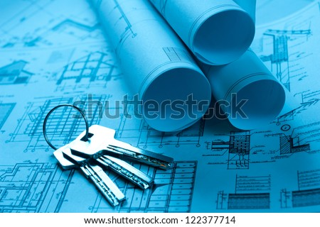 scrolls of technology blueprint with keys from house - stock photo