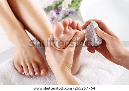Scrub, scrub with pumice dead epidermis.Foot care treatment and nail, the woman at the beautician for pedicure. - stock photo