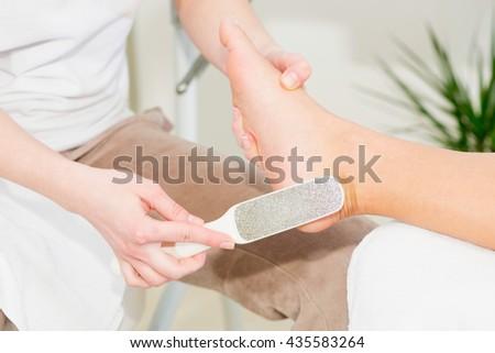 Scrubbing heel on pedicure treatment - stock photo