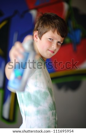 Scruffy boy pointing spray can at camera with graffiti wall in background.
