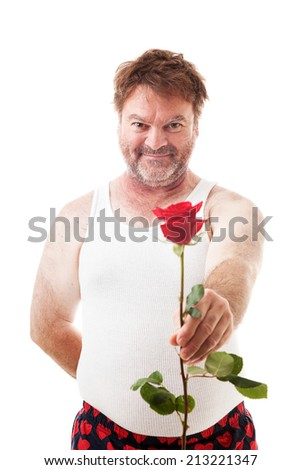 Scruffy looking man in his underwear holding out a single red rose for his sweetheart.  Isolated on white.