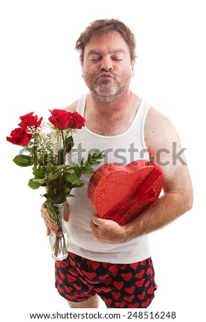 Scruffy middle aged man in his underwear with flowers and candy for Valentines Day, puckering up for a kiss.  Isolated on white.   - stock photo