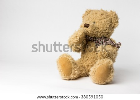 Scruffy teddy bear with copper kettle on white background