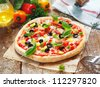 Scrumptious homemade pizza with a thick golden base topped with cheese, tomato, pepper, olives and herbs - stock photo