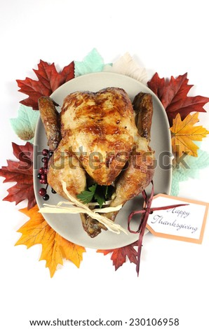 Scrumptious roast turkey chicken on platter with festive decorations for Thanksgiving lunch with autumn Fall leaves on white table.  - stock photo