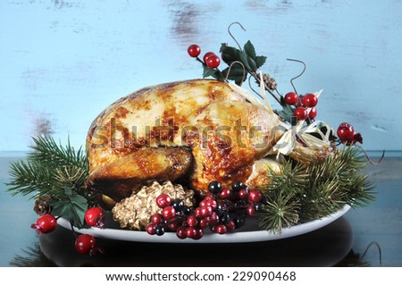 Scrumptious roast turkey chicken on platter with festive decorations for Thanksgiving or Christmas lunch, against shabby chic aqua blue rustic wood background. - stock photo