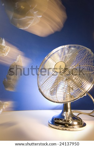 Scrunched up A4 paper being scattered through the air by a retro styled desk fan. Suitable for random distribution, none responsible recycling policy, discarded ideas, scatter thoughts etc. - stock photo