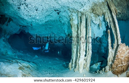 Scuba diver exploring a narrow section of a cenote on the Yucatan Peninsula, Mexico. - stock photo