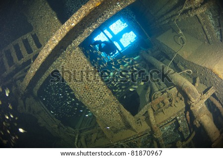 Scuba diver exploring inside the engine room of a large shipwreck - stock photo
