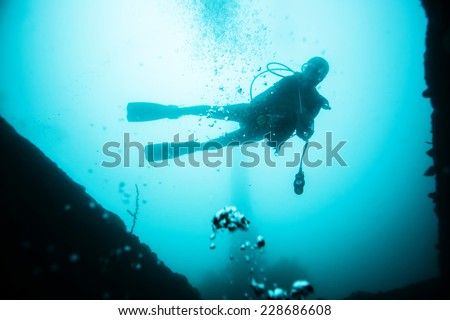 Scuba diver exploring world war II shipwreck in Coron area, Palawan, Philippines.  - stock photo