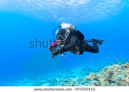 Scuba diver floating over coral reef in the Red Sea. - stock photo