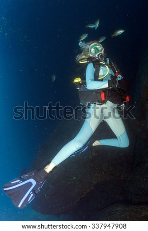 scuba diver in fish and corals reef blue ocean background - stock photo