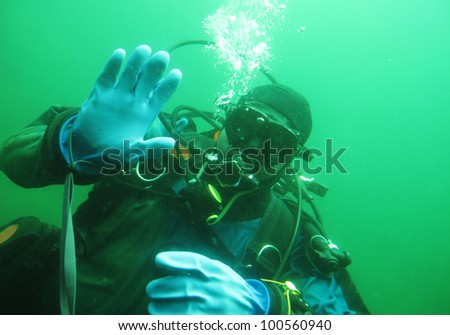 Scuba diver in freshwater. Diving in cold depth lake. - stock photo