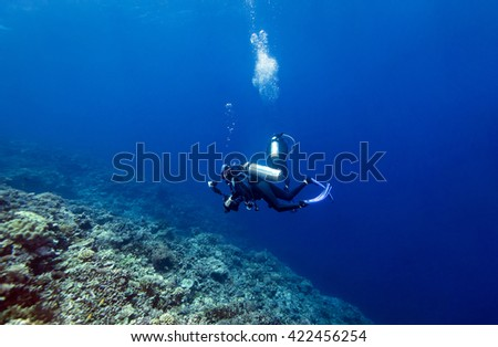 Scuba diver in tropical coral reef, Layang Layang. - stock photo