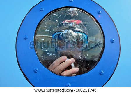 Scuba diver is diving in a water tank. - stock photo