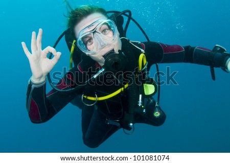 scuba diver makes OK sign underwater - stock photo