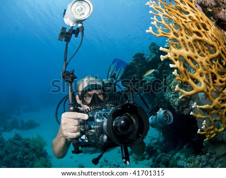 scuba diver man with underwater camera - stock photo
