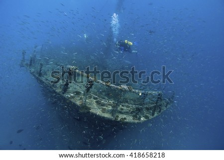 Scuba diver on a wreck in blue water surrounded by thousands of fish. - stock photo
