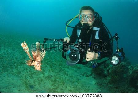 Scuba Diver photographer and Lionfish - stock photo
