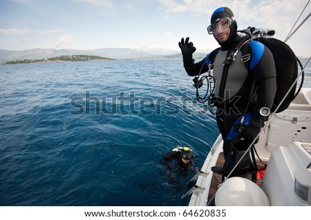 scuba diver standing on the yacht and ready to dive - stock photo