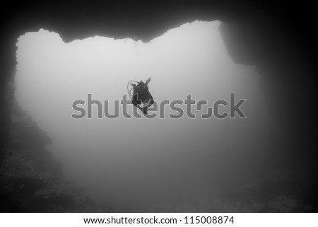 Scuba diver swimming into the Blue Holes Dive Site off the islands of Palau in Micronesia. - stock photo