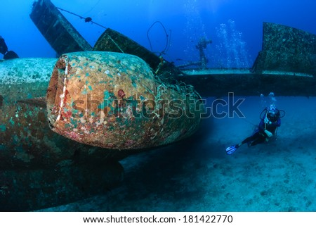 SCUBA diver swimming next to the jet engine attached to the wreckage of a sunken aircraft