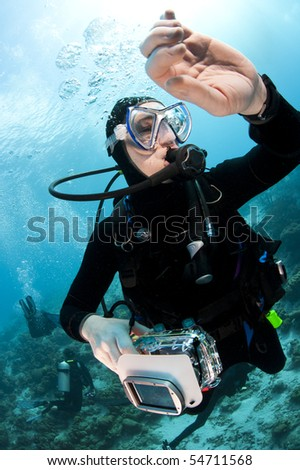 Scuba diver swimming over a tropical coral reef in Bonaire, Netherlands Antilles with her camera checking her dive watch during a safety stop.