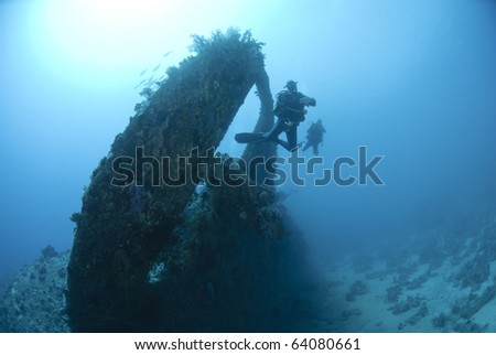 Scuba diver swimming through the propellor area of a shipwreck. Dunraven, Beacon rock, Red Sea, Egypt. - stock photo