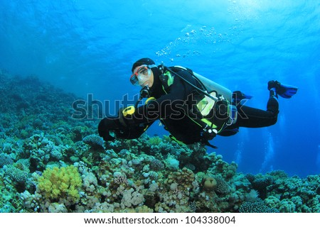 Scuba Diver swims over coral reef - stock photo