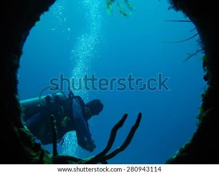 Scuba Diver through porthole.  Cozumel Mexico.                             - stock photo