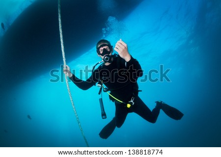 Scuba Diver underwater of the big blue sea making safety stop after a dive holding the line underneath the boat at depth from 3 to 6 meters to release the nitrogen saturated in his body after a dive. - stock photo