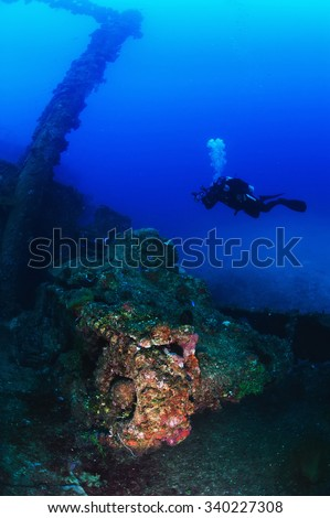 Scuba diver underwater photographer swimming over WWII tank on the deck of ship wreck   full sea anemones and corals.30 meters depth. Truk Lagoon.Micronesia. - stock photo