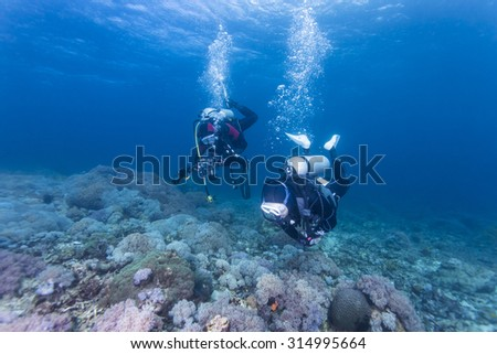Scuba diver with a camera swims over a colorful tropical coral reef. - stock photo